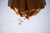 hands sprinkling seeds