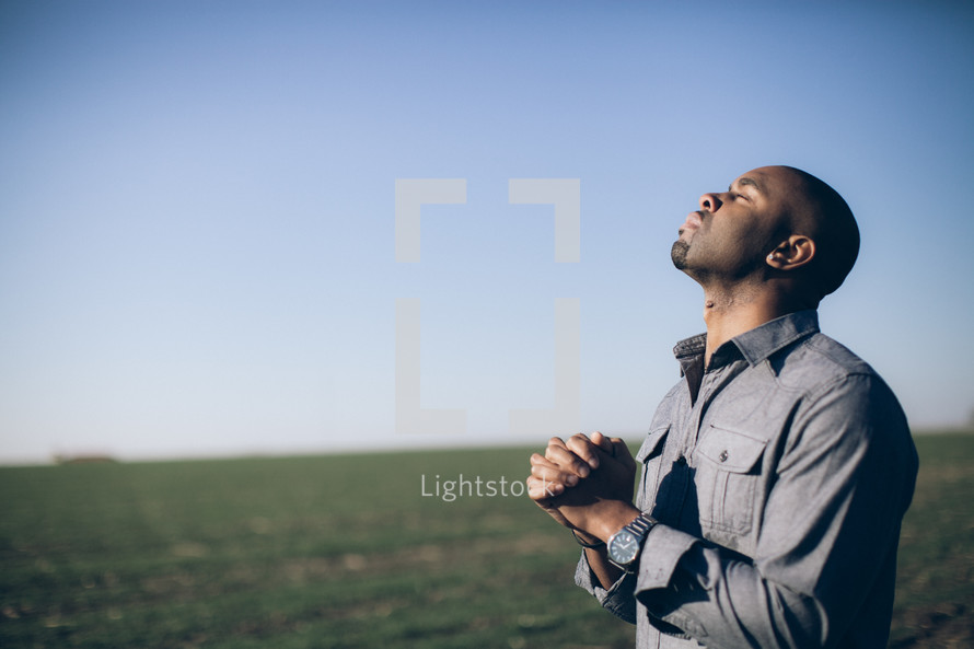 man with his hands held in prayer and his head tilted to God