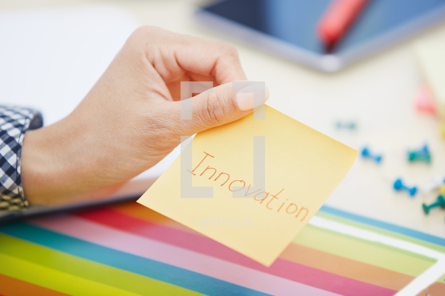 woman holding a sticky note with the word innovation