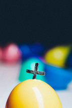 Cross emerging from a plastic Easter egg.