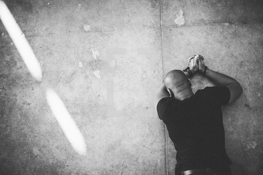 man lying on the ground in prayer repenting