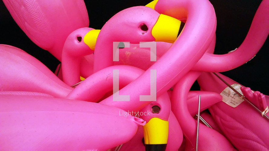 A group of Pink Flamingo plastic birds with metal stakes are gathered to put together