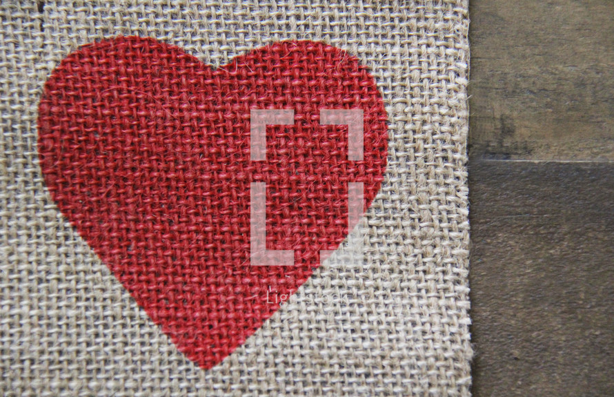 red heart on burlap on wooden background
