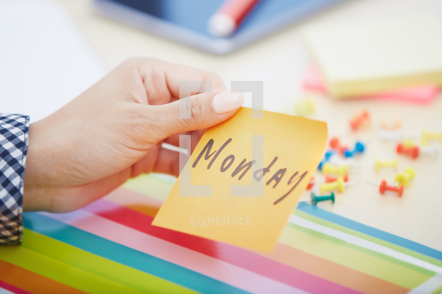 woman holding a sticky note with the word Monday