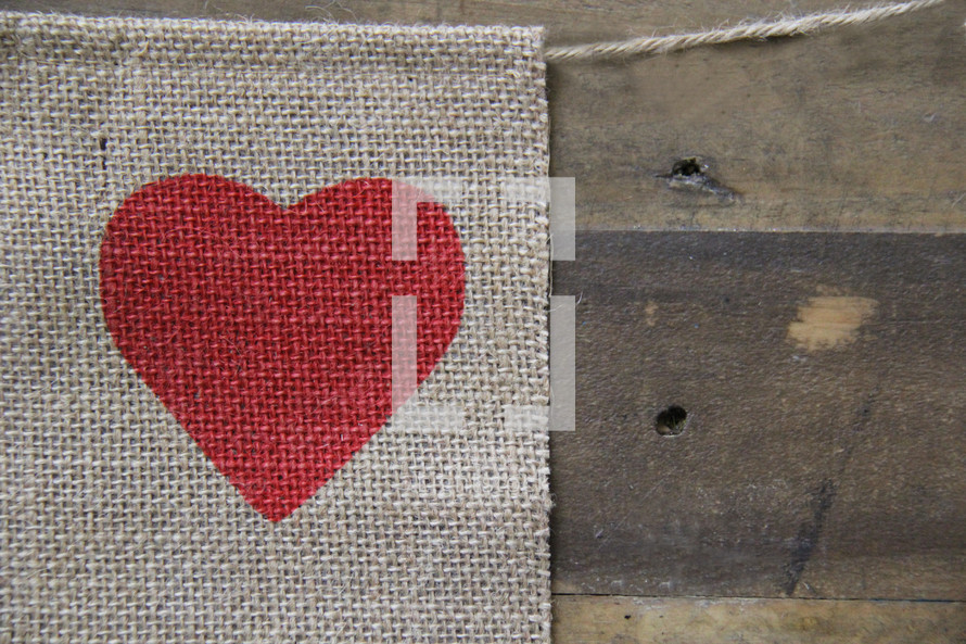 heart on a burlap banner over a wooden background
