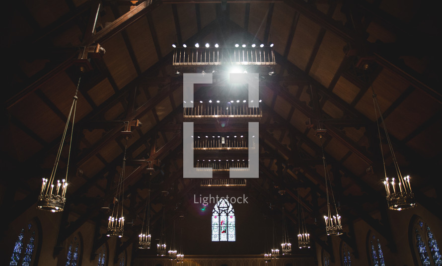 Candelabras hanging from a soaring church ceiling.