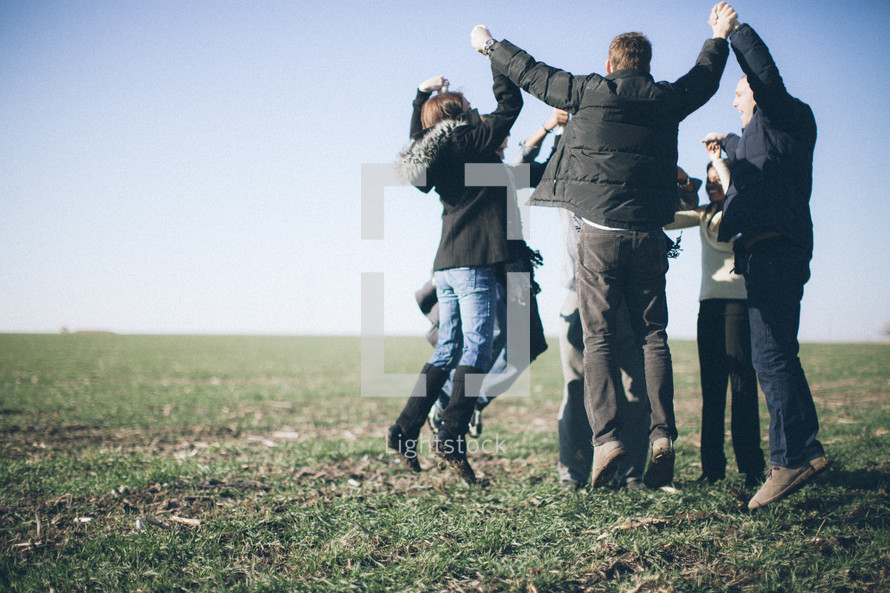 a group holding hands in a circle and jumping in the air in celebration