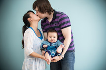 Kissing couple cradling their infant child.