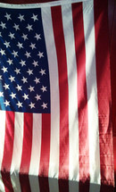 The United States Flag draped over a wall as a banner to represent freedom, democracy, truth, honor and be a beacon of hope to all who come to this country seeking freedom from persecution or longing for a better way of life.