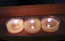 Three wax candles burning together during a candlelight worship service during Christmas Eve or some other occasion at church.