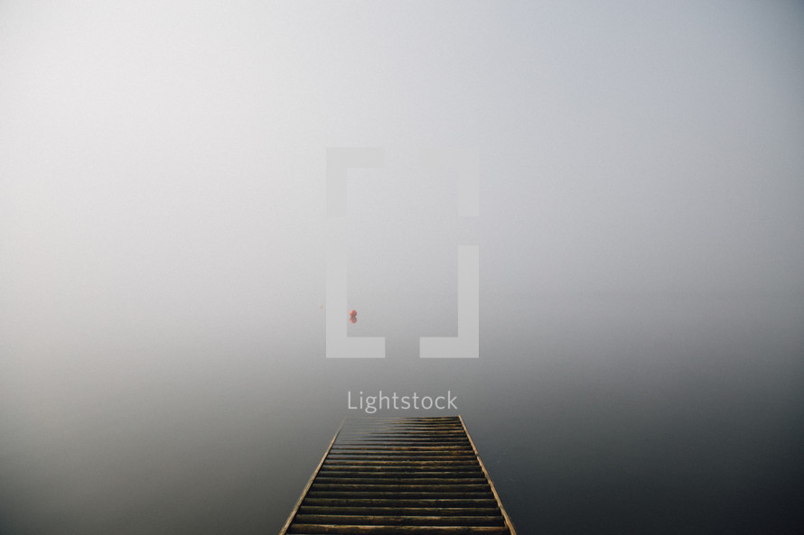 Misty view from a wooden pier.