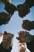 group holding hands in prayer