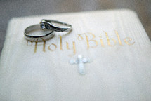 Two wedding rings set on top of a white bible.