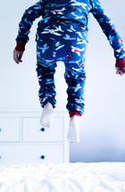 a boy in pajamas jumping on a bed
