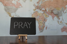 world map and word pray on a sign