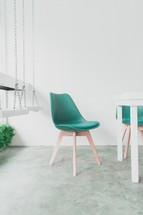 green chairs around a table and indoor swings