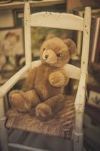 A teddy bear sitting in a rocking chair