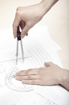 woman using a compass on blue prints