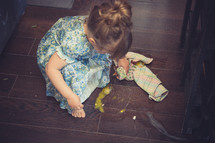 toddler girl cleaning up a mess on the kitchen floor