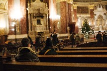 people sitting in pews of a cathedral at Christmas