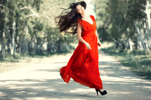 a woman jumping in a red dress
