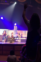 woman standing with raised hand at a worship service
