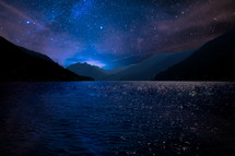 stars in the nights sky and water in a bay surrounded by mountains
