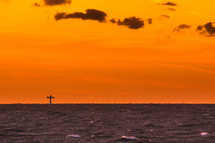 Sunset over the ocean with a cross in the distance.