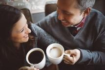 a couple toasting coffee mugs