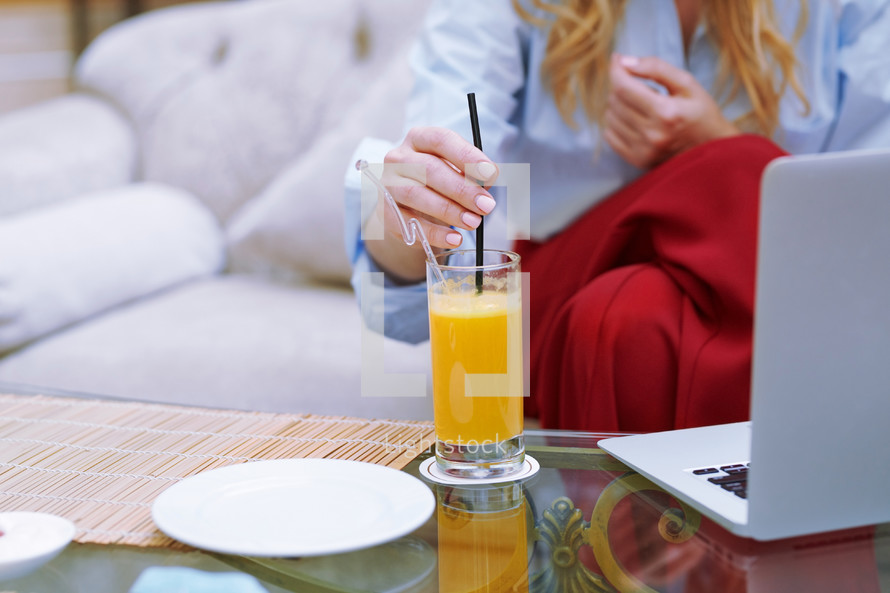 woman drinking orange juice and working in a lobby