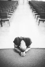 man kneeling in prayer at the altar of a church