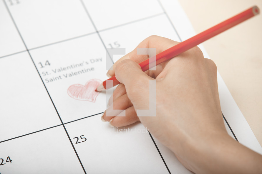 Woman hand drawing heart on a calendar at Valentine Day