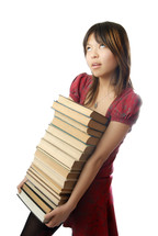 Young schoolgirl carrying numerous heavy books