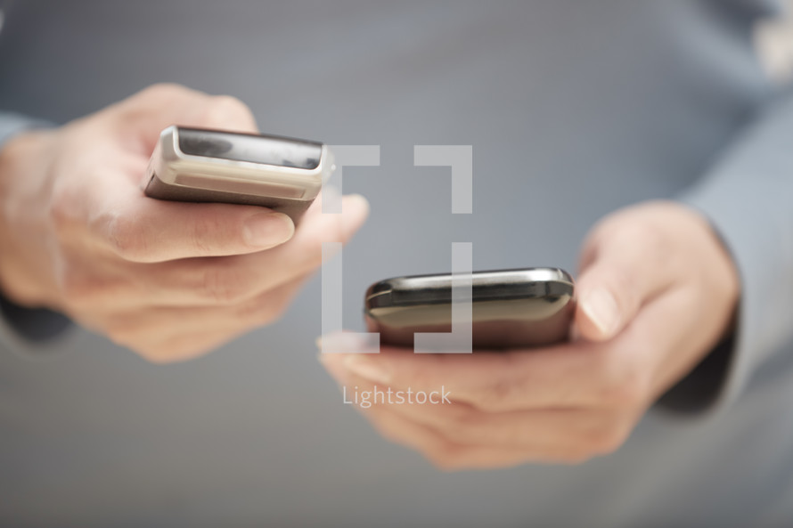 person holding two cellphones