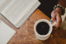 woman reading a Bible and a mug of coffee