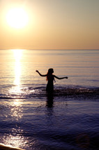 a young woman walking into water at sunset