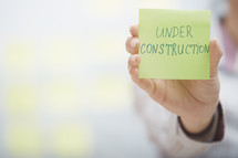 a woman holding a sticky note with the words under construction