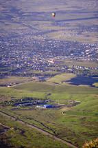 hot air balloon over a green valley