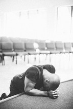 Man with head on hands praying on empty stage.