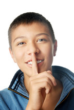 Smiling boy with finger on his lips