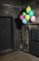 balloons on a radiator in a dark hallway