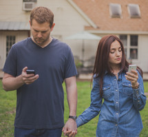 couple holding hands talking checking their phones