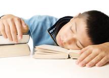 a kid sleeping on books