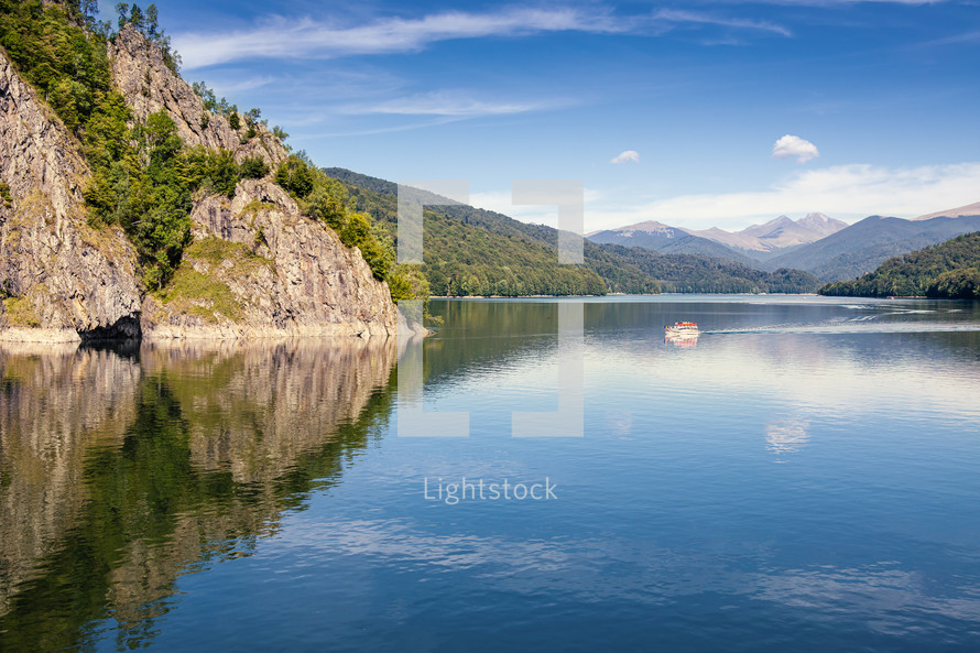 Daylight view to Vidraru lake in Carpathian Mountains. Bright blue sky and green trees. Boat cruising on water.