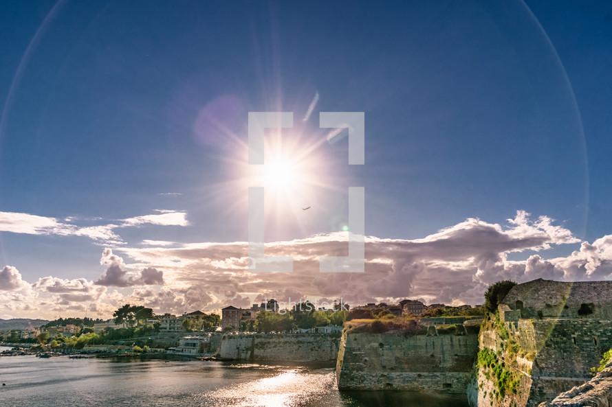 sunburst over cliffs along a shore