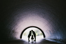 silhouettes of a mother and father kissing in a tunnel and a child standing between them