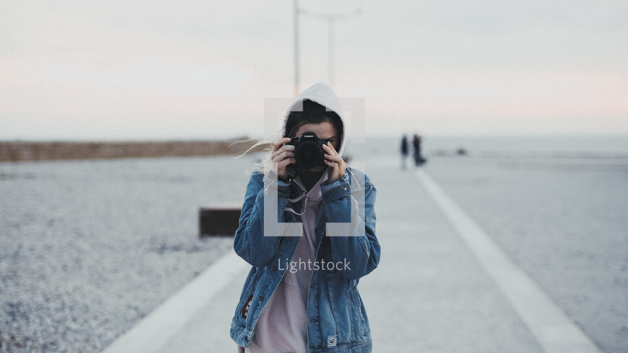 a woman standing on a pier taking picture with a camera