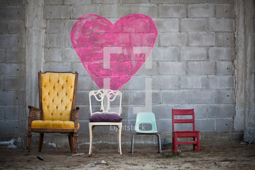 Family chairs in the dirt by a heart painted on a brick wall.