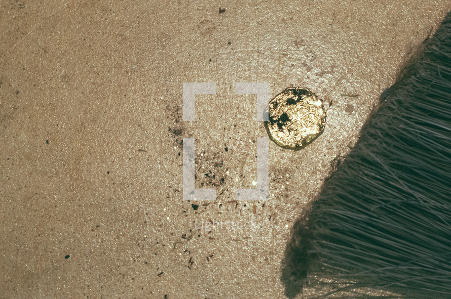 dirty gold coin and broom