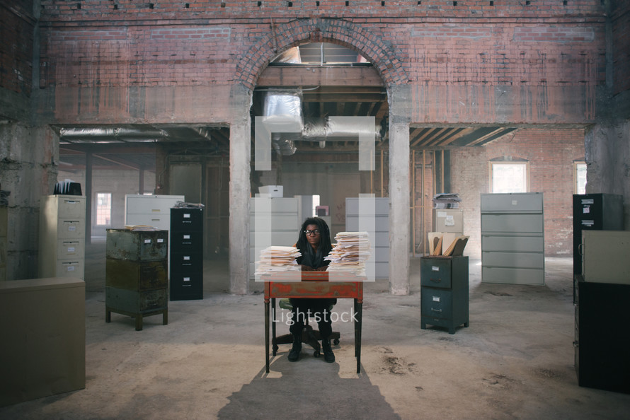 an overworked woman standing behind a desk covered in files